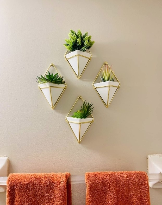 Three white/brass, geometric planter vases mounted to a wall