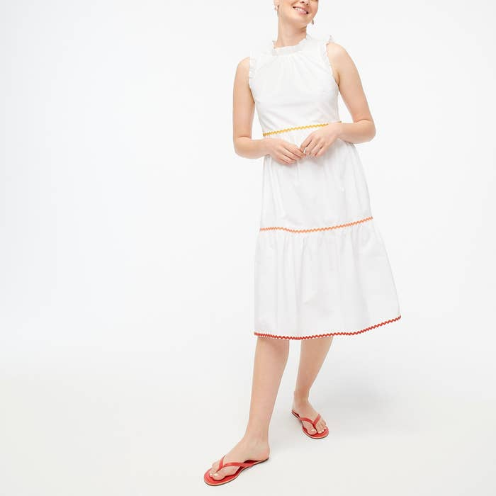model wearing white dress with colored rickrack trim