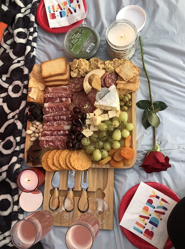 A bamboo cheese board with a pull out tray underneath filled with 4 utensils
