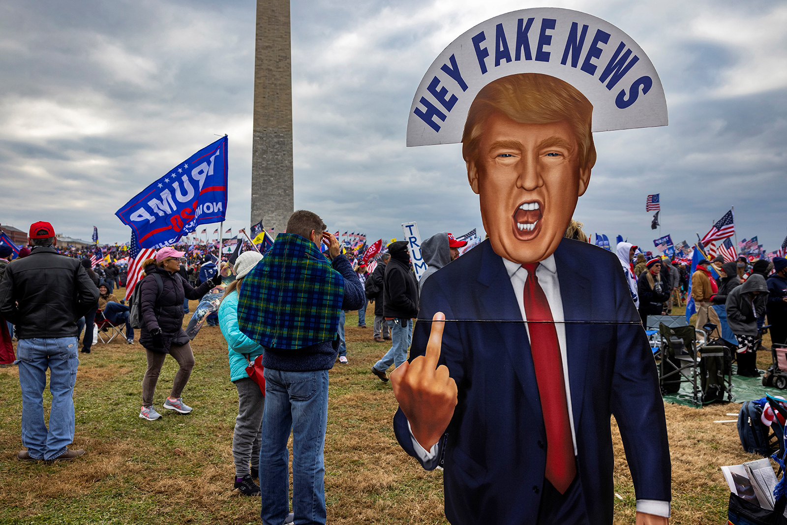 """People stand near a cardboard cutout of Trump with a sign reading """"Hey Fake News"""" over his head as he flips off the camera"""