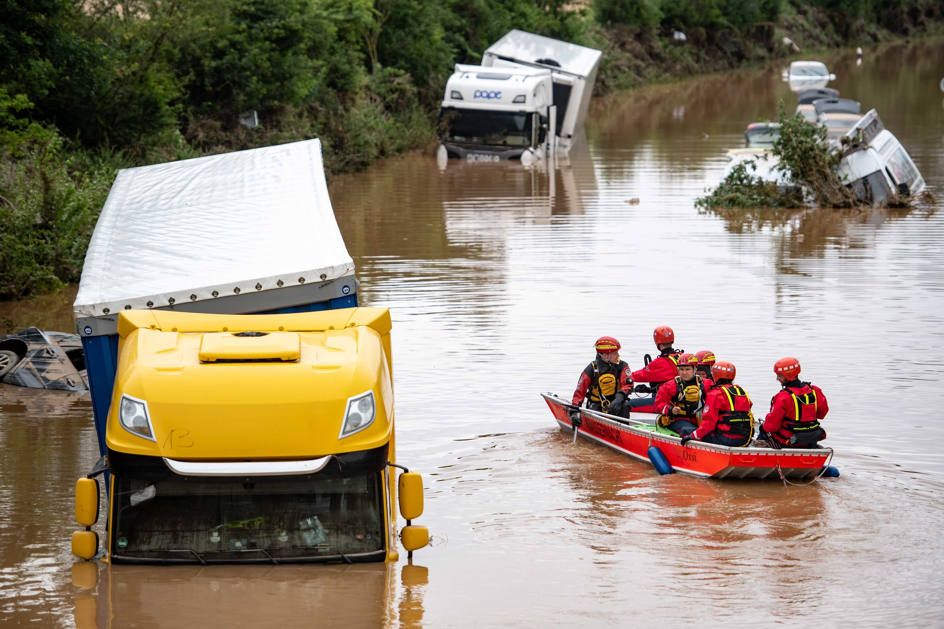submerged trucks on a highway are approached by firefighters in a boat