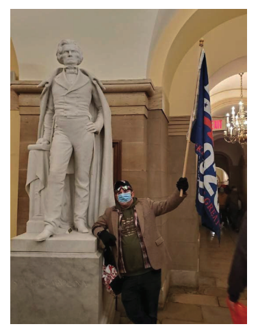 A man holds a large Trump flag while leaning on a statue in the Capitol