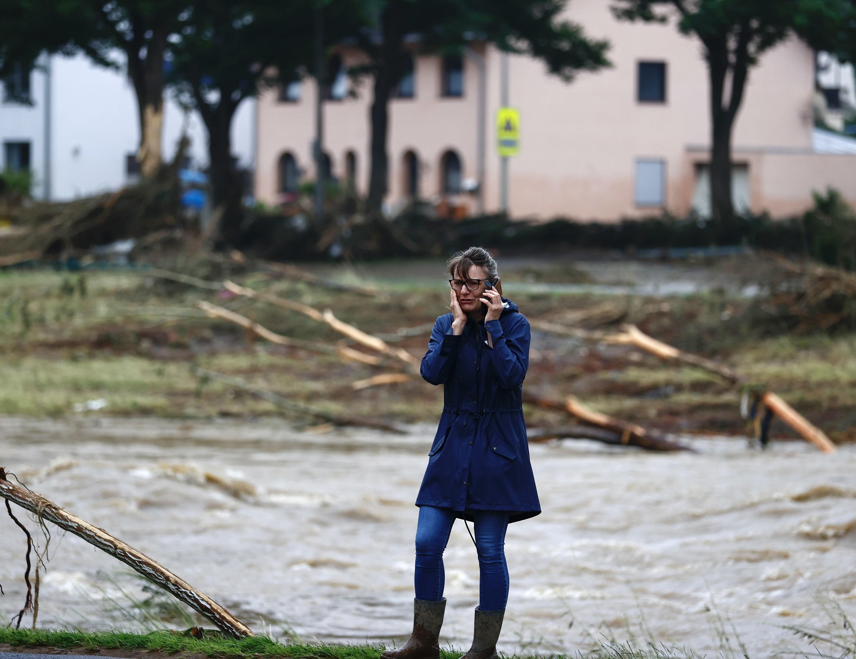 A woman on the phone looking worried with floodwaters in the background