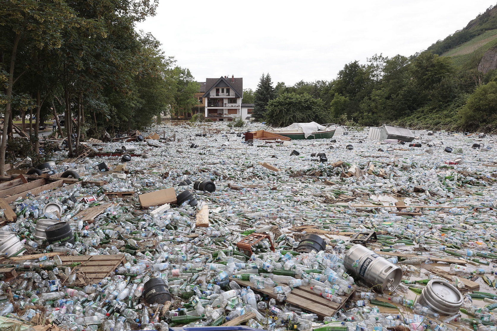 A large area of ground is covered in plastic water bottles, glass bottles, and beer kegs