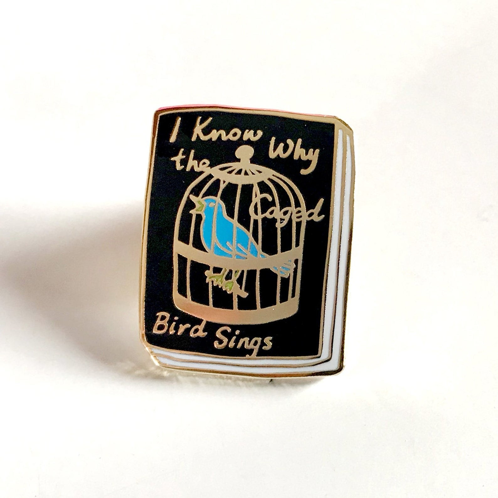 """Pin that looks like the book """"I Know why the caged bird sings"""" on it with a blue bird in a cage signing"""