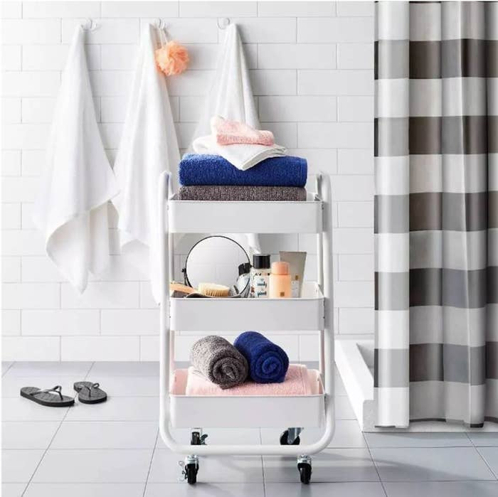 White utility cart with towels bottom rack, hair products middle rack, towels top rack