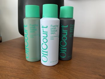 Green, white, and black spray bottles with green tops