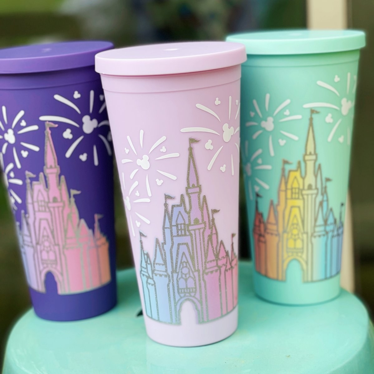 three tumbler cups with the disney world castle and fireworks above it