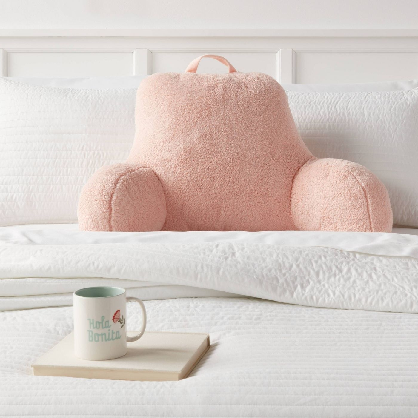 light pink bed rest pillow on a bed with white linens on it