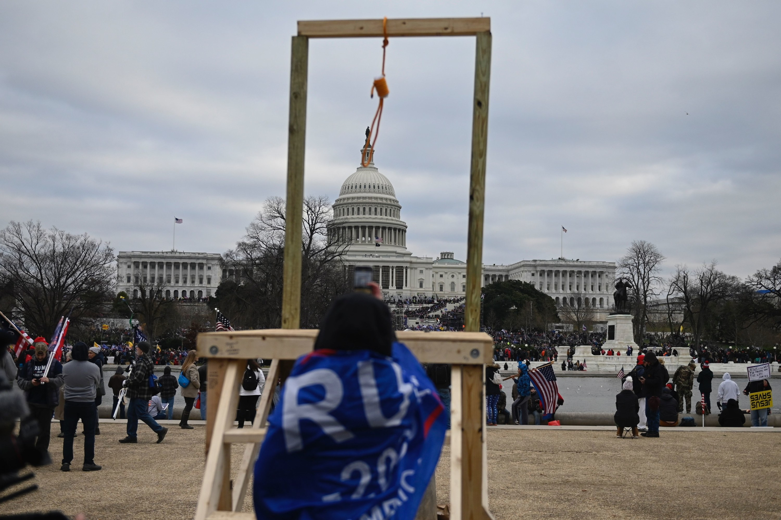 A person draped in a Trump flag stands in front of gallows with a noose that rioters put up in front of the Capitol