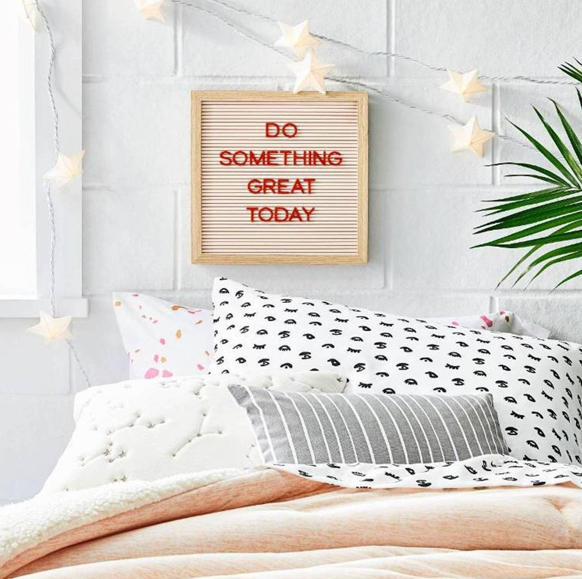 """square letter board that says """"do something great today"""" hung on a wall in a dorm room"""