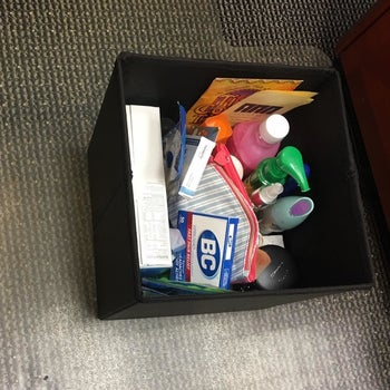 same reviewer's storage ottoman with the top off revealing beauty and healthcare products in it
