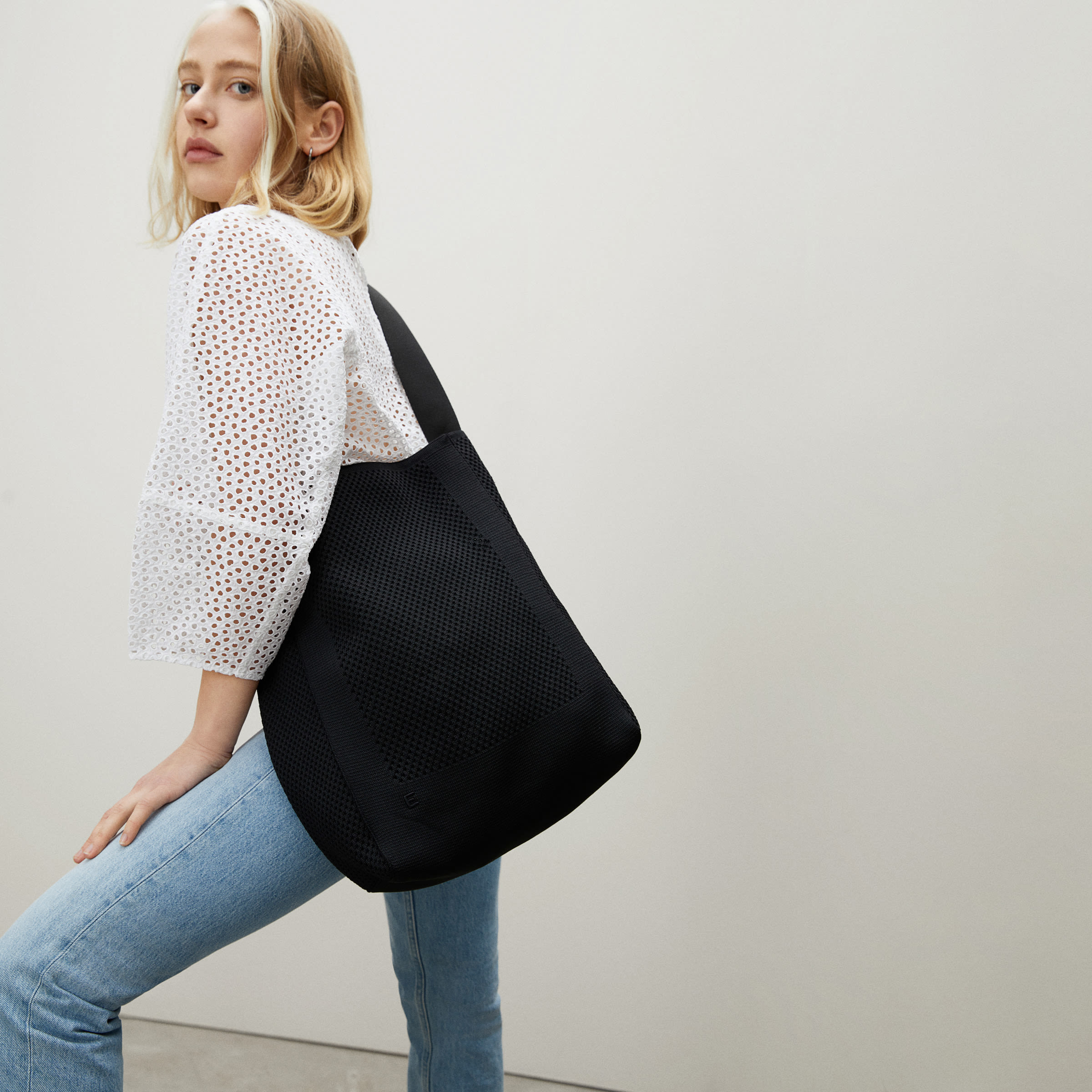 a model holding the black oversized tote bag