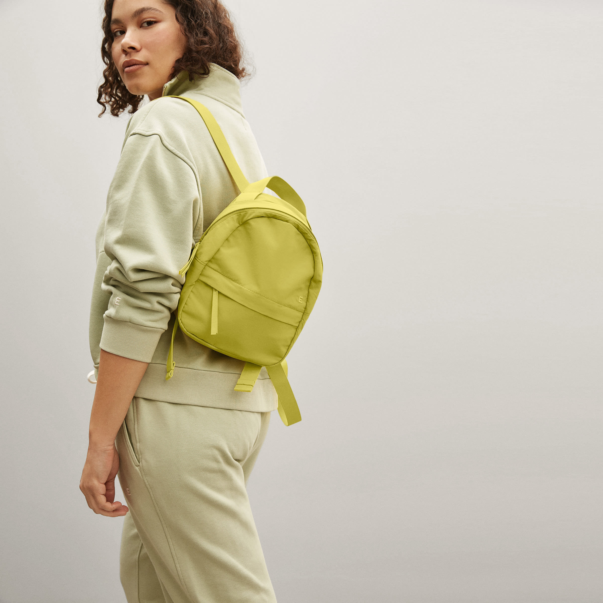 a model carrying a small yellow backpack
