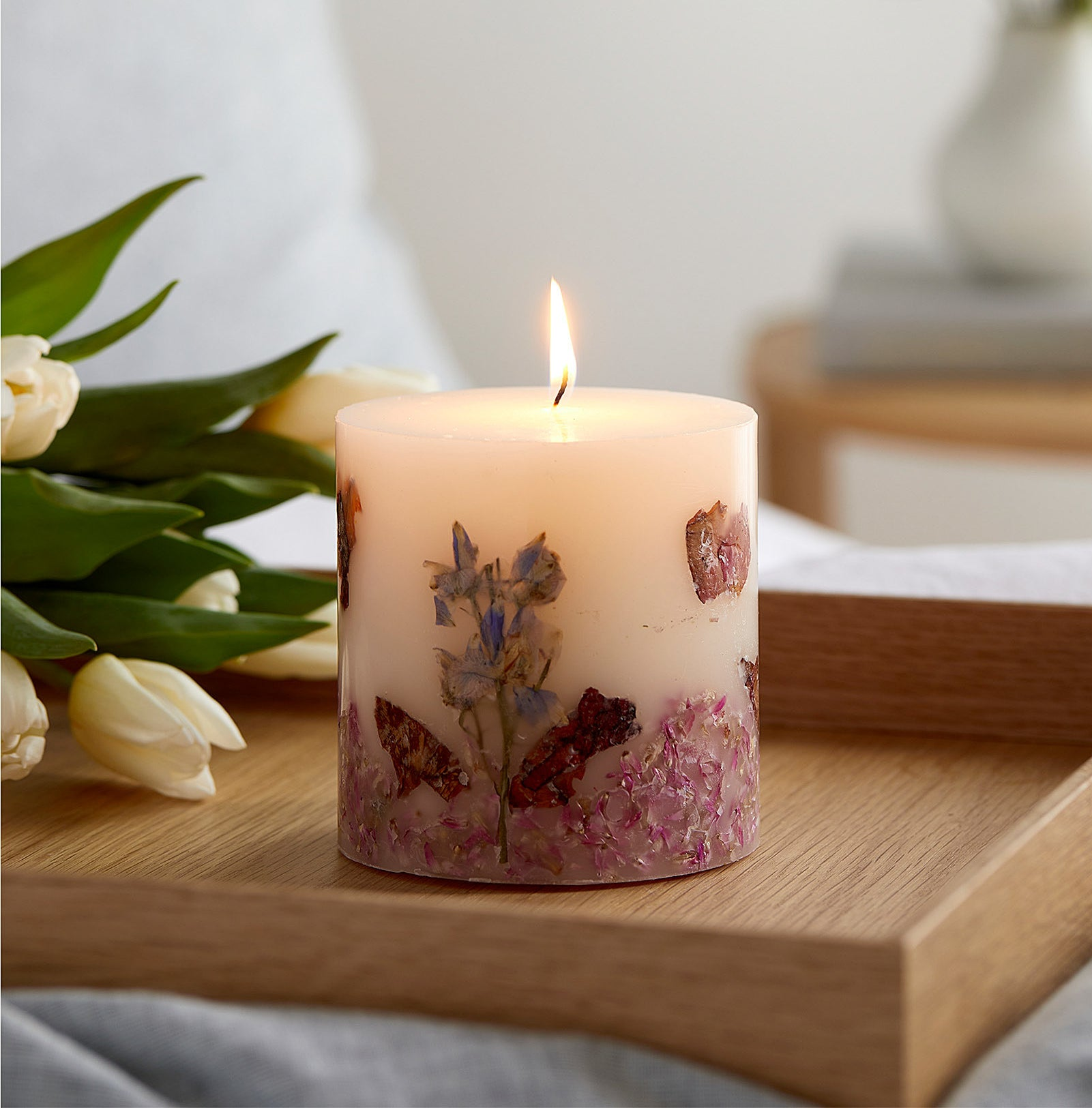 a lit candle on a tray next to a bouquet of tulips