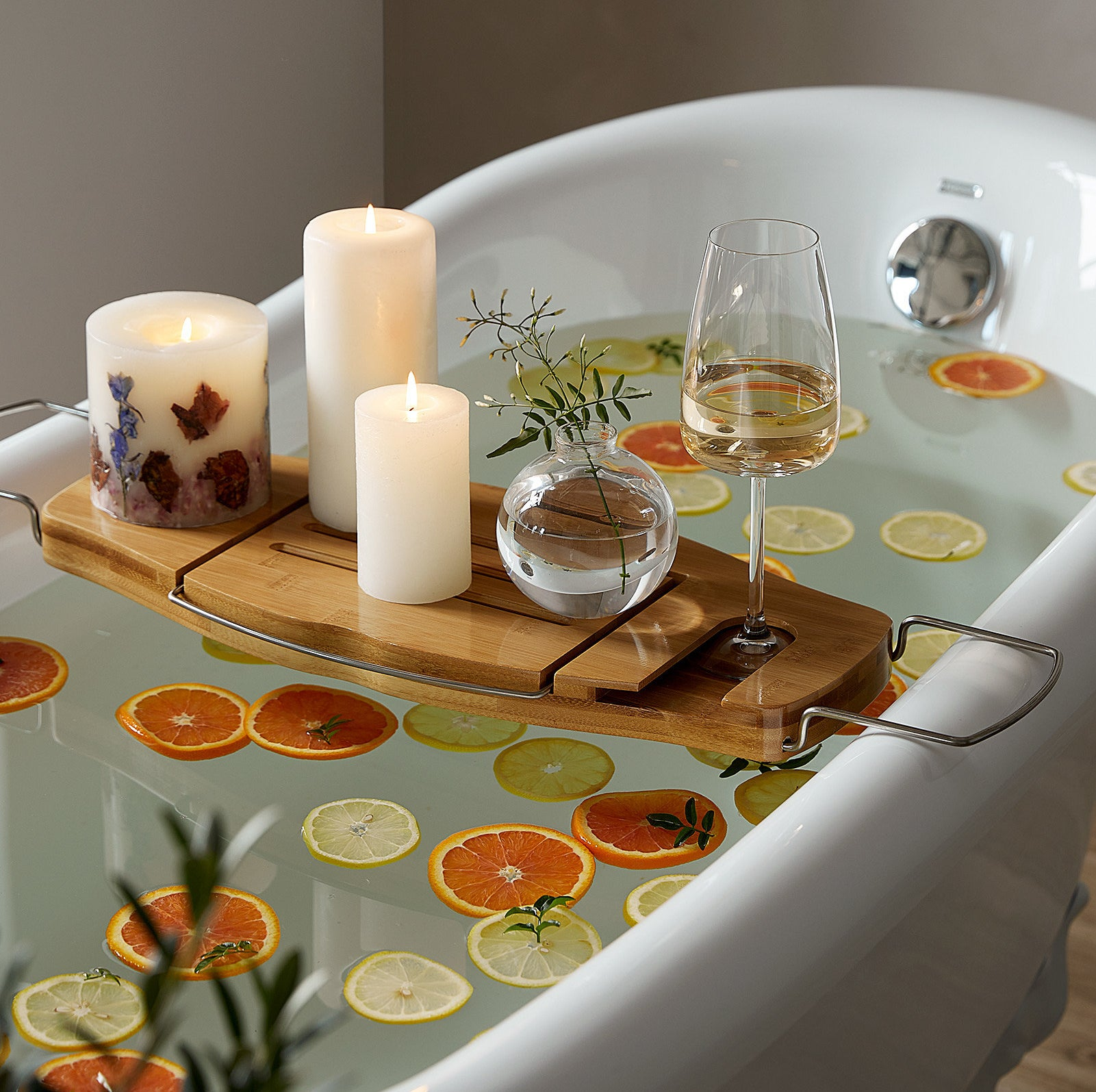 a tub filled with citrus slices with the tub tray on top holding candles and wine