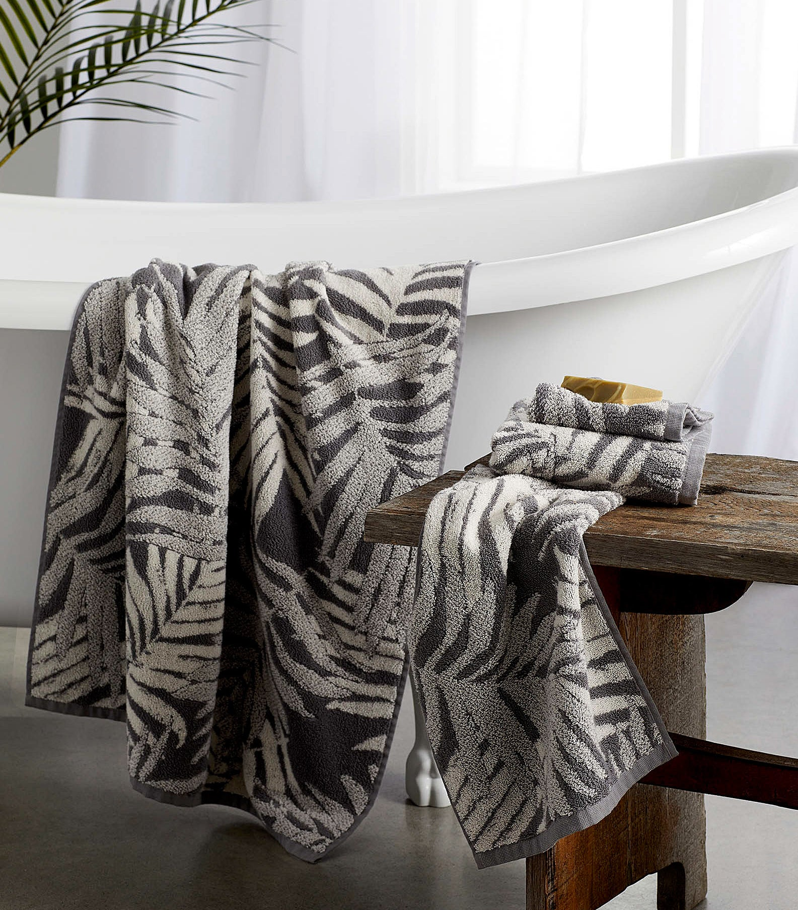 two towels with palm leaf patterns in a bathroom