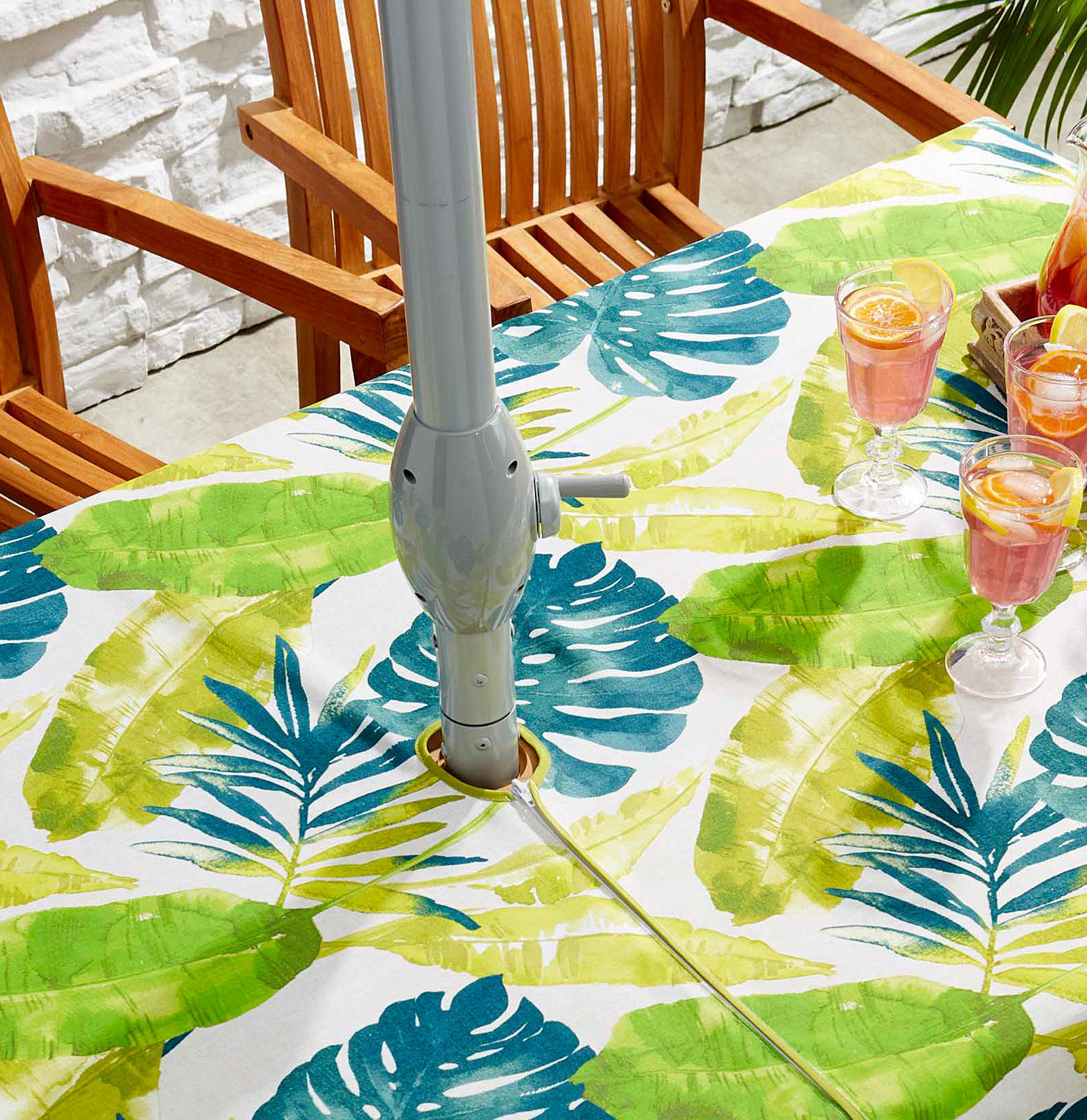 a botanical patterned table cloth on a patio table with a hole for the umbrella