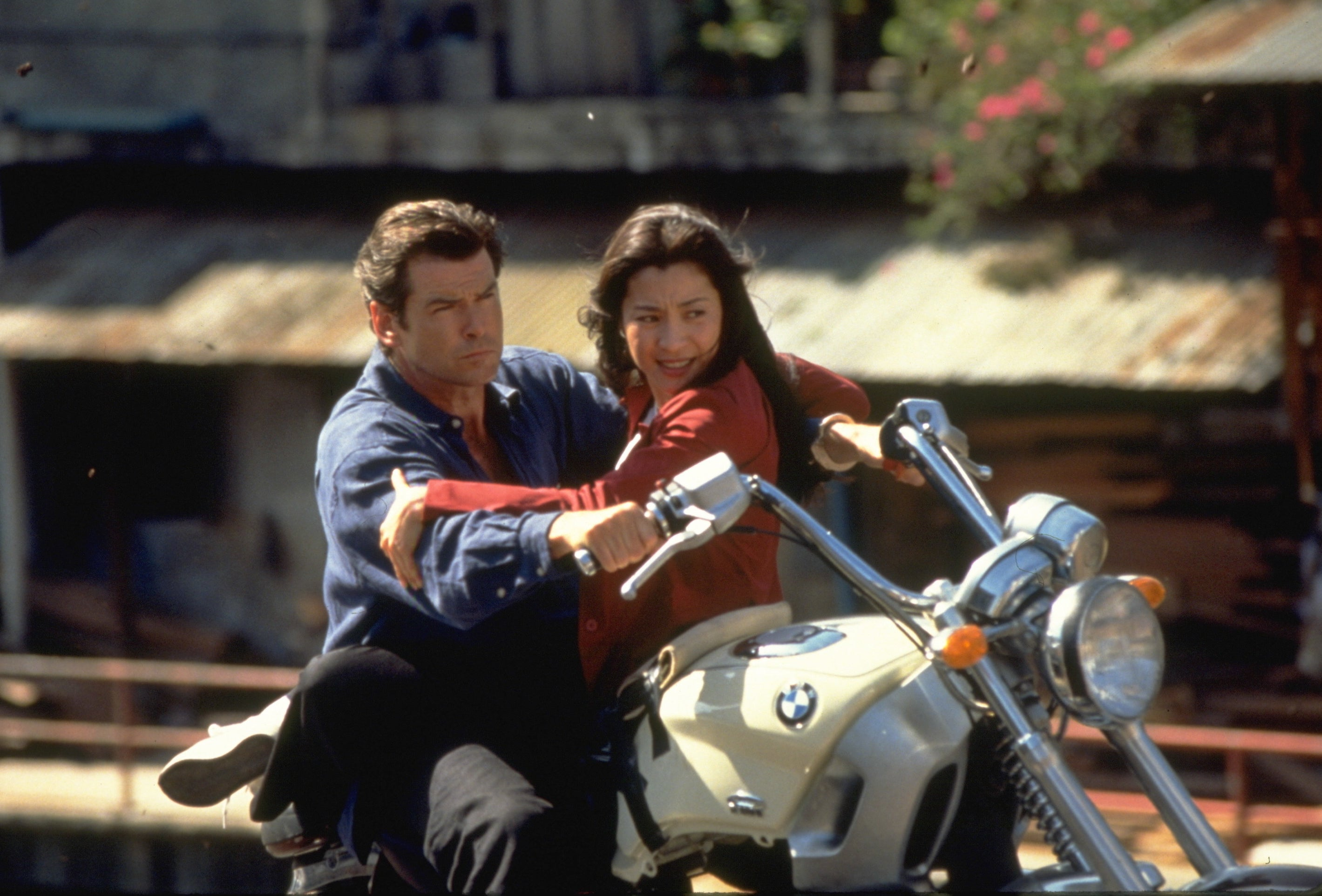 A man and a woman riding a motorcycle with the woman sitting in front of the man and facing the man.