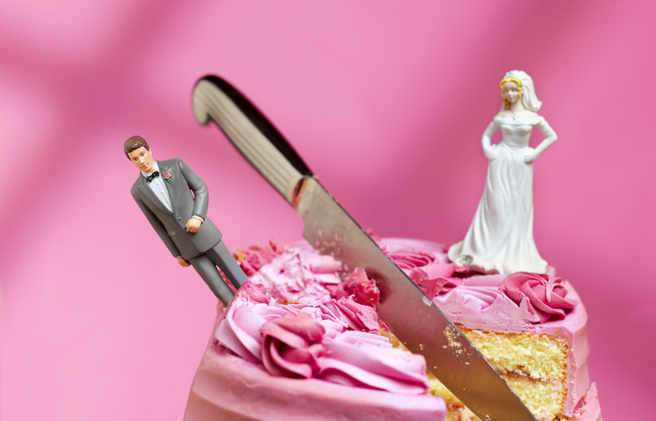 A knife cutting into a cake between figurines of a bride and groom