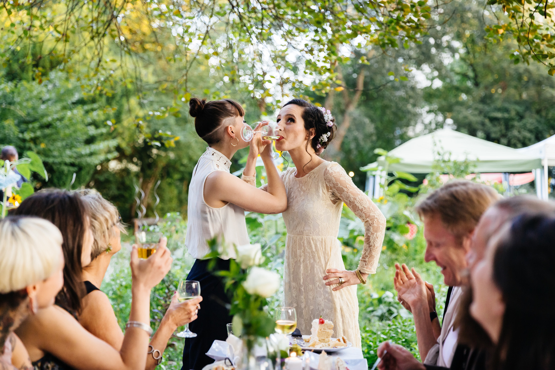 Two people sipping from glasses with their arms intertwined at a wedding