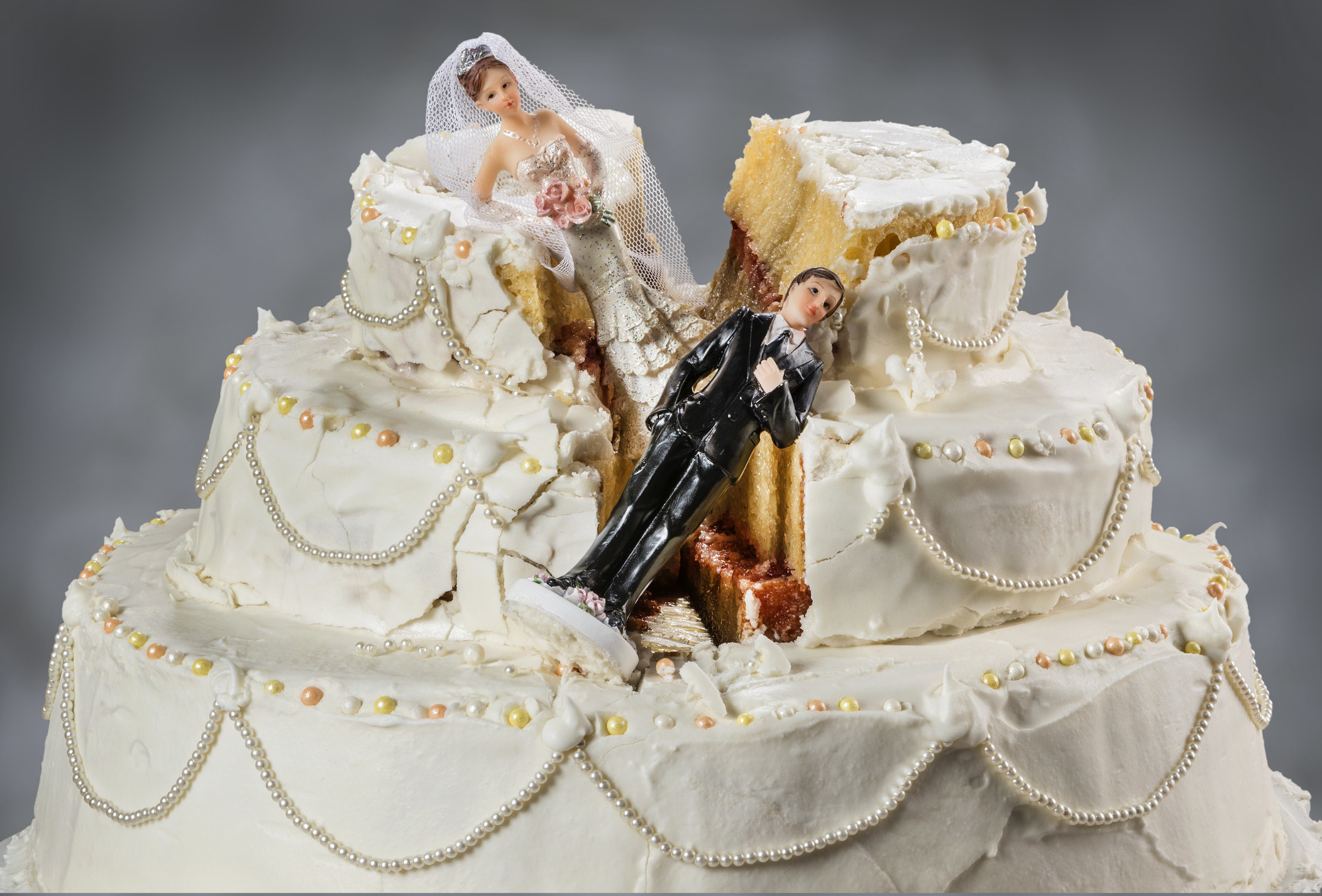Figurines of a bride and groom falling down a split wedding cake