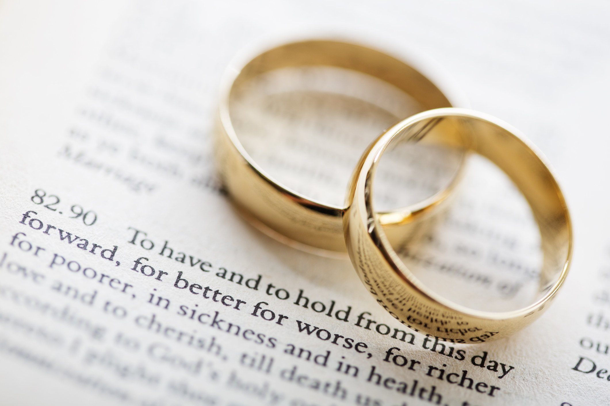Two wedding bands on top of a piece of paper with vows print6ed on it