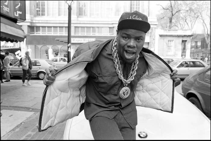 Biz Markie holding his jacket open to show his thick necklace