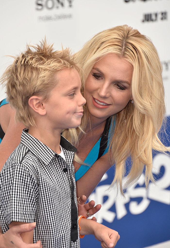 Britney kneeling down to hug one of her sons, Sean Preston Federline