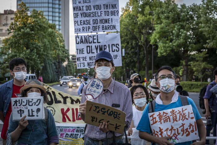 """People wearing masks and signs in Japanese and English (""""Cancel the Olympics"""")"""