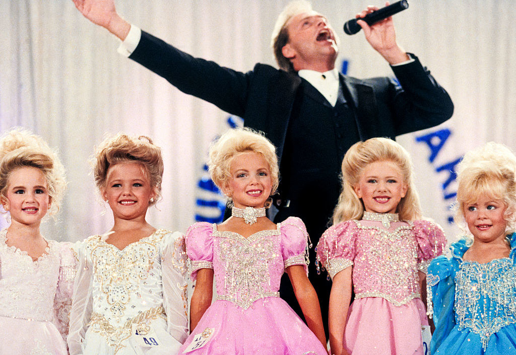 Five young girls in makeup and dresses in a beauty pageant with an announcer behind them