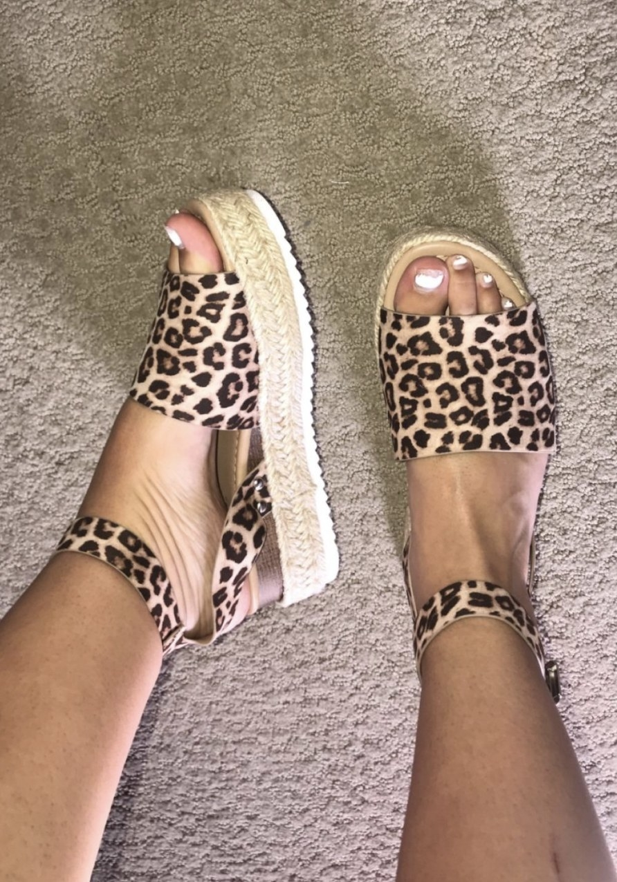 a reviewer wearing the sandals in leopard