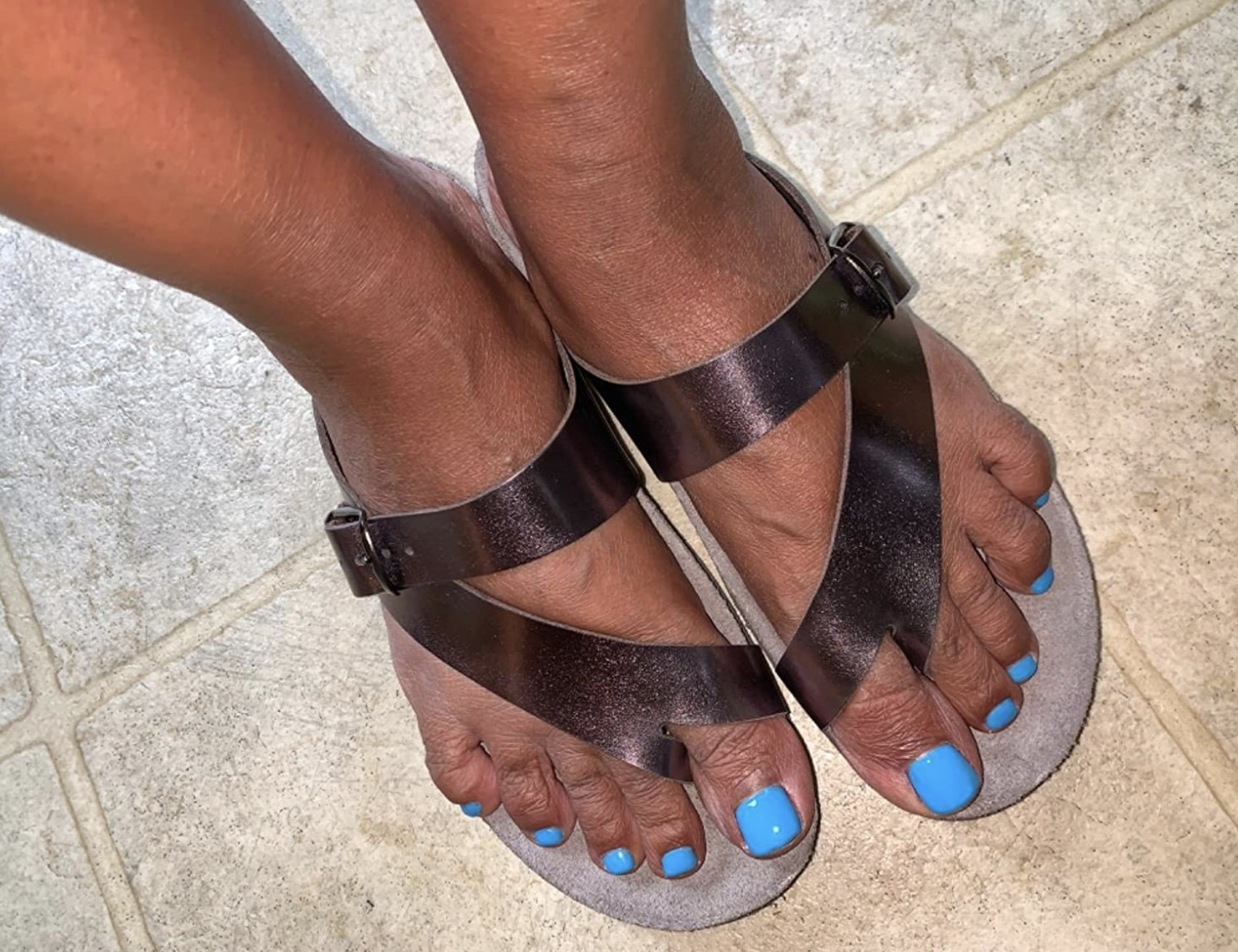 a reviewer wearing the sandals in bronze