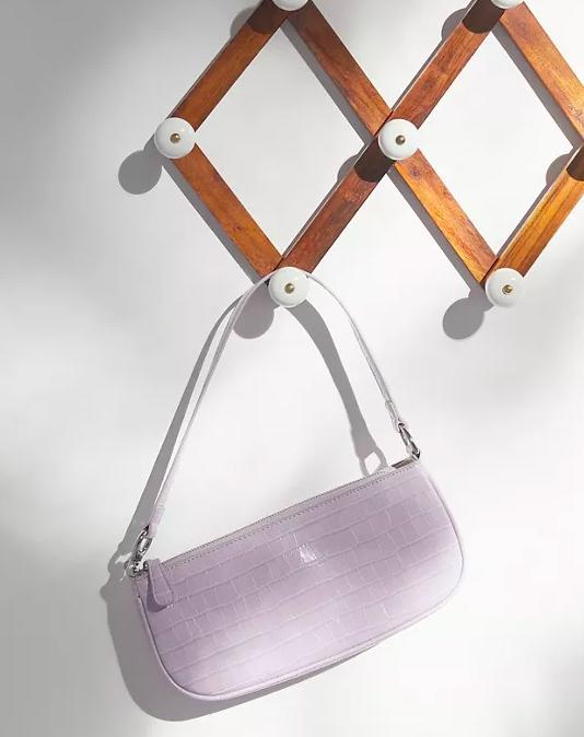 the crocodile print purse hanging on a hanger