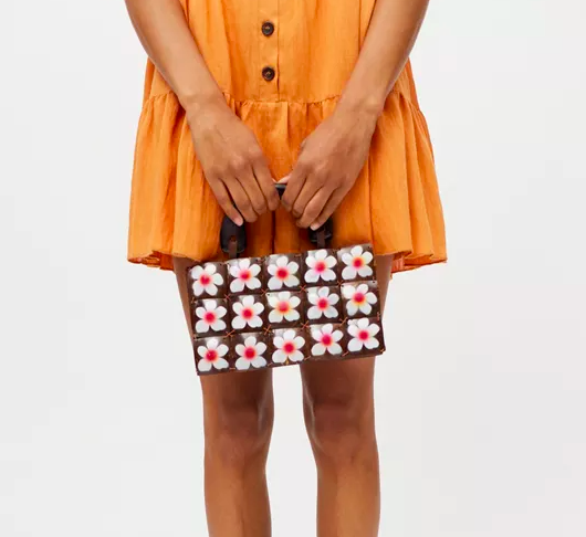 a person holding the flower-print purse while wearing a vibrant dress