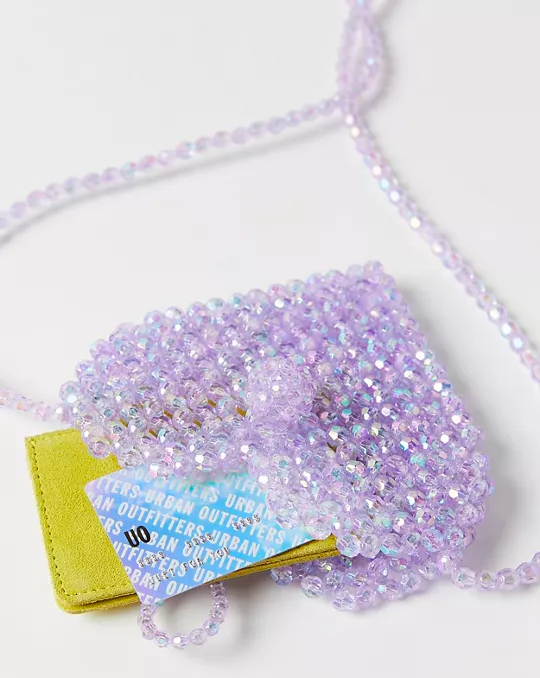 a beaded heart-shaped purse with a wallet and a card sticking out the top