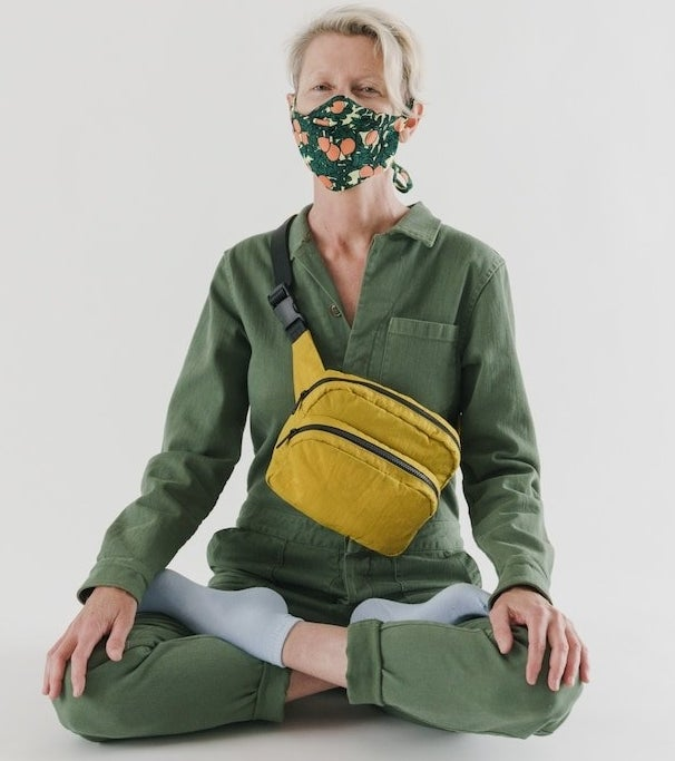 a person sitting cross legged wearing a mask and the large fanny pack