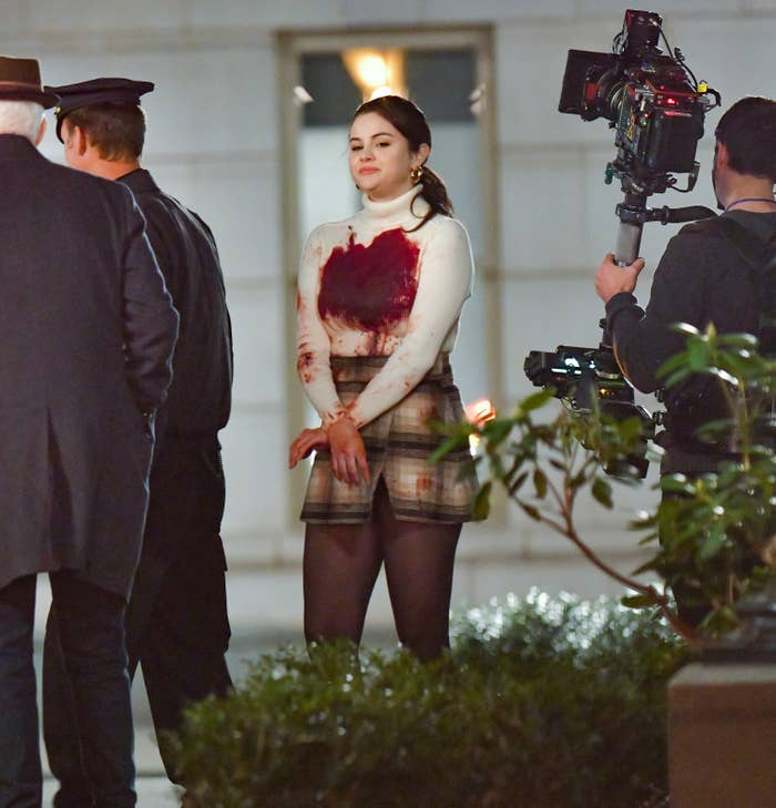 Selena filming a scene while wearing a blood-stained turtleneck and a plaid skirt