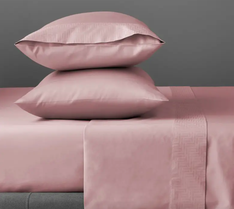 The pillowcases on pillow stacked up on a bed in pink