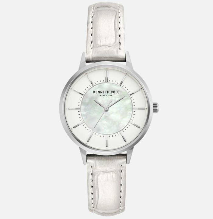 """A white, metallic leather watch with a mother of pearl dial face with """"KENNETH COLE NEW YORK"""" written on face"""