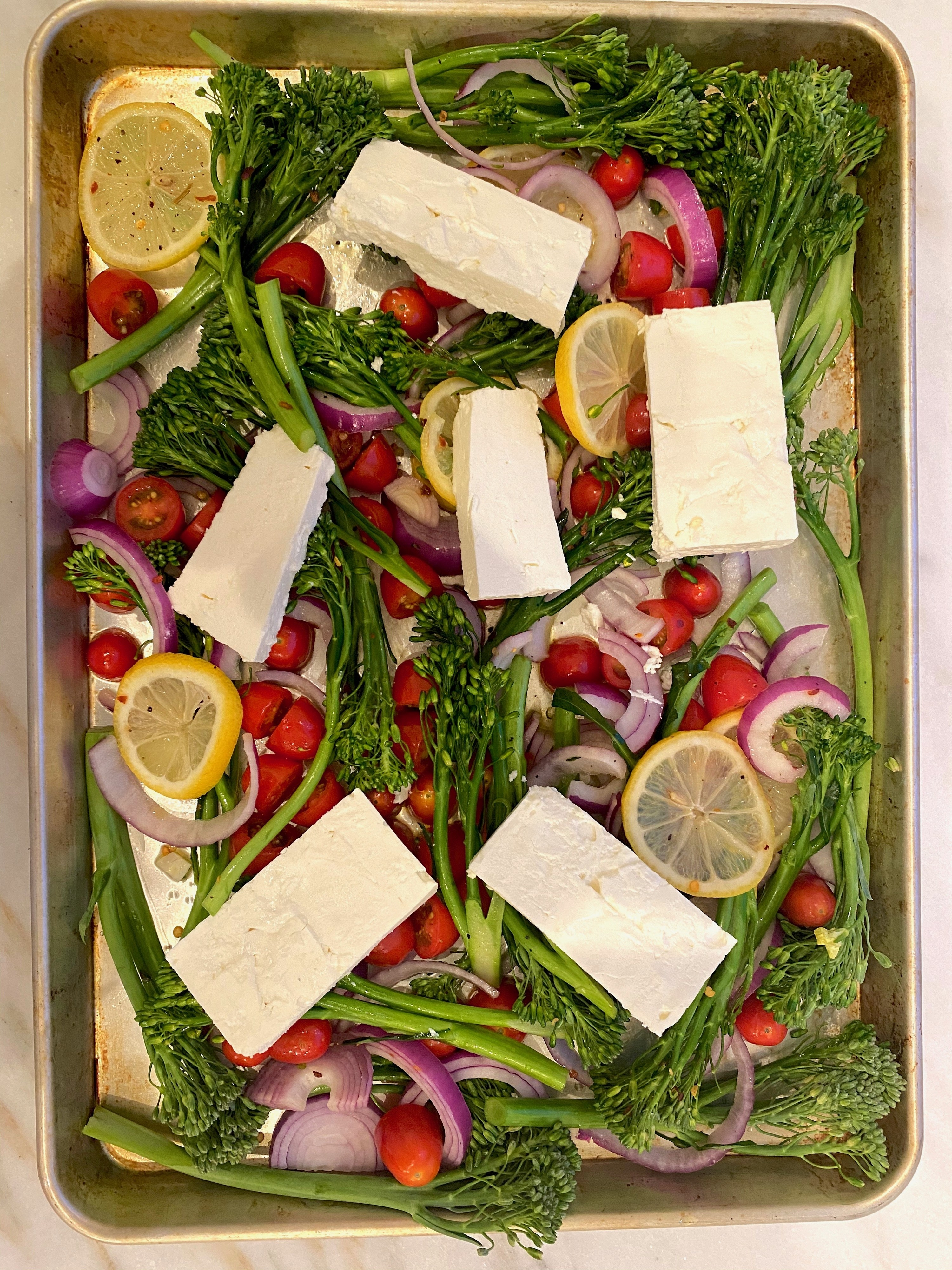 Vegetables on a sheet pan with blocks of feta