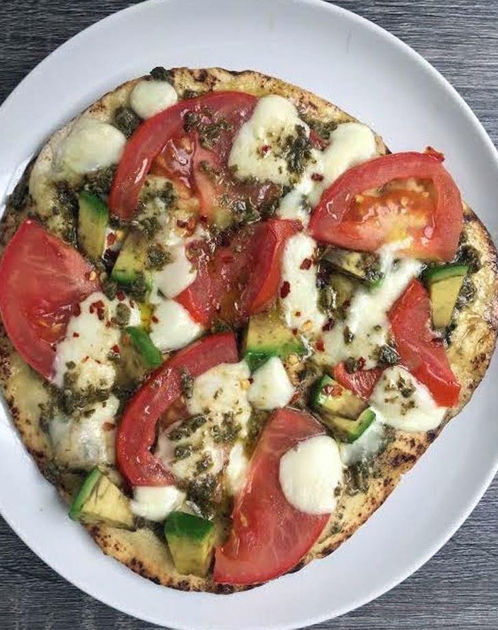 A naan pizza with tomatoes, avocado, mozzarella, and pesto