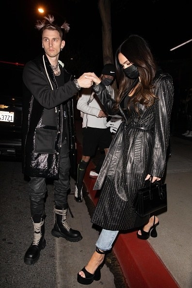 he holds her hand to help her step down from a steep curb