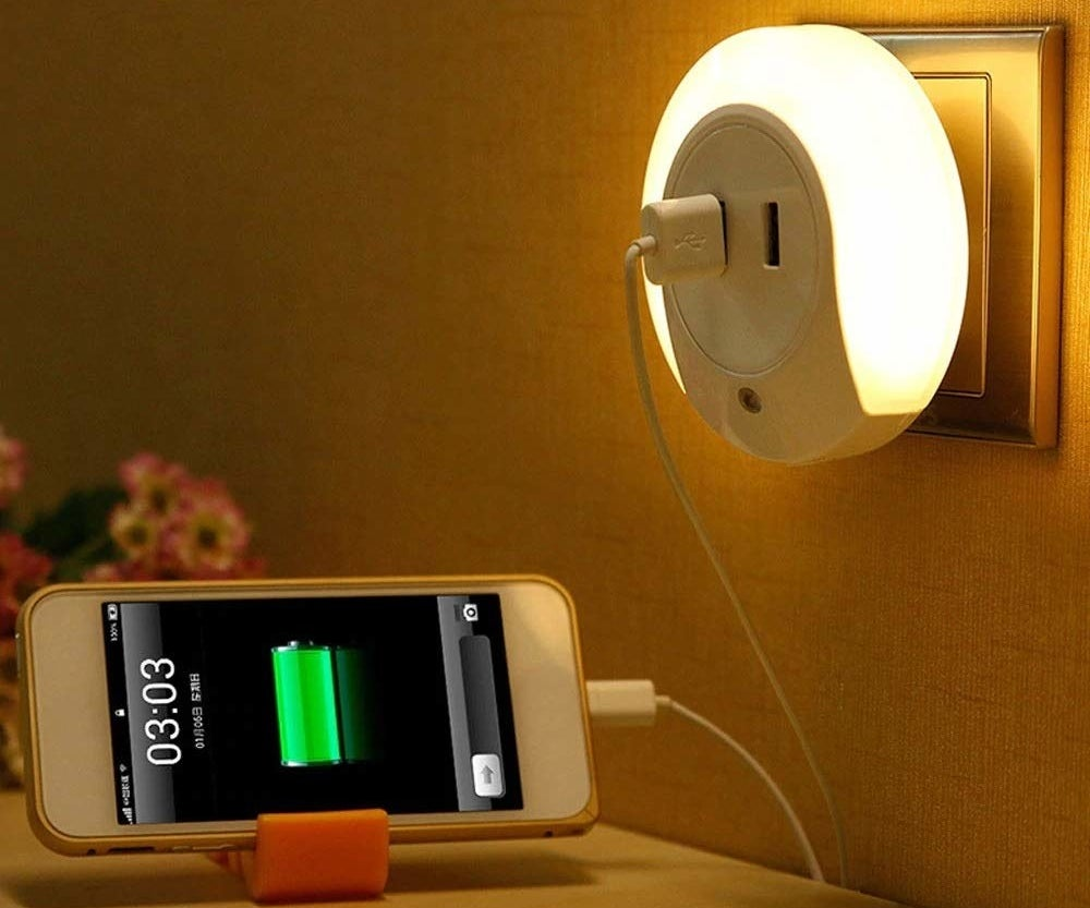 A USB night lamp plugged into a wall socket charging a phone