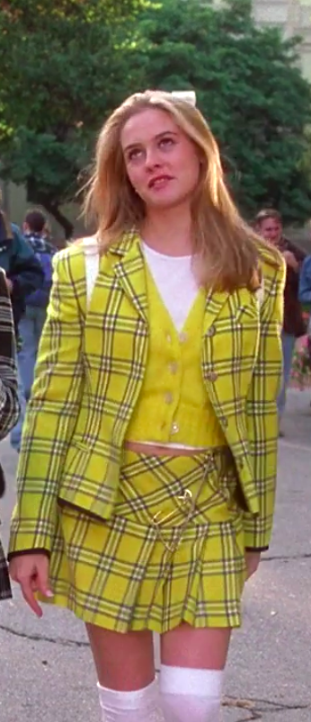 Cher wearing knee-high socks, a mini skirt, a t-shirt, a cardigan, a jacket matching the skirt, and a small fluffy backpack