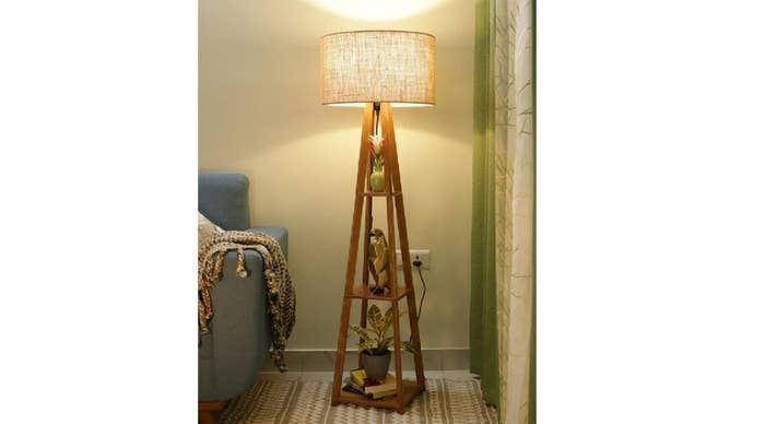 A lamp with three shelves between its legs that are holding plants and other decor items