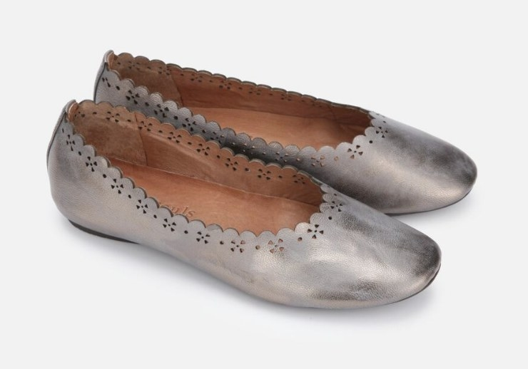 A pewter, metallic ballet flat with scalloped trimming and cut out details