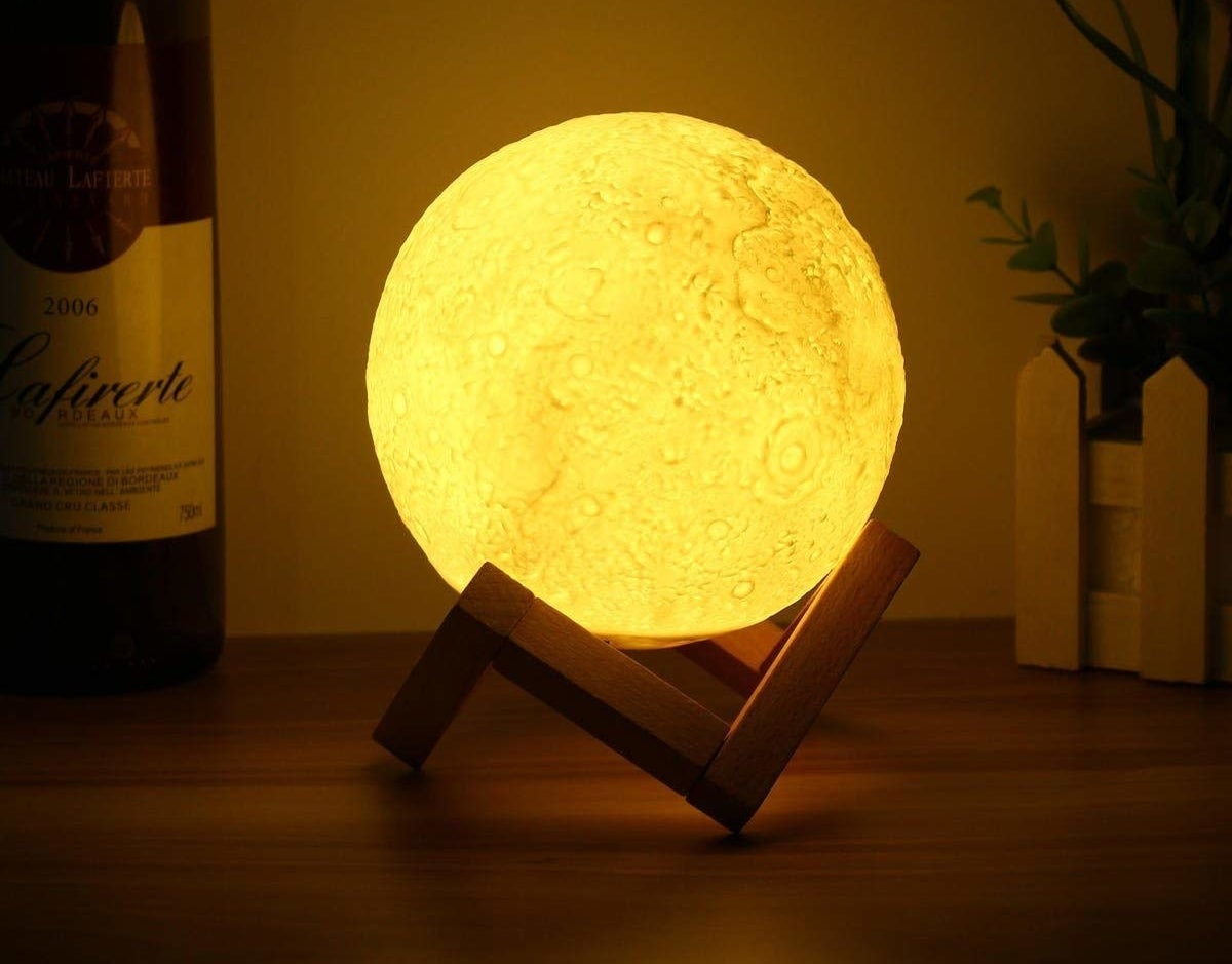 A moon lamp on a wooden stand
