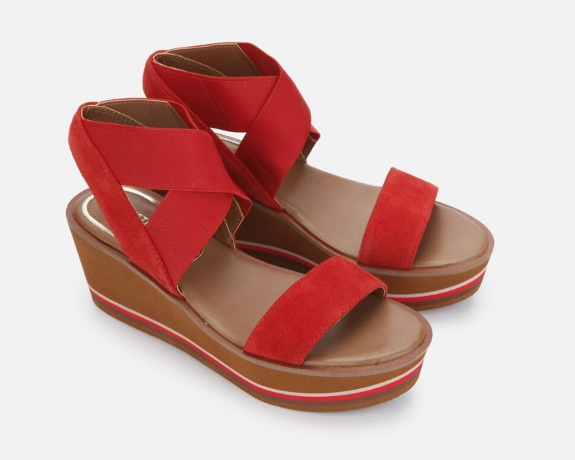 A platform sandal with red, suede straps and a cushioned foot bed