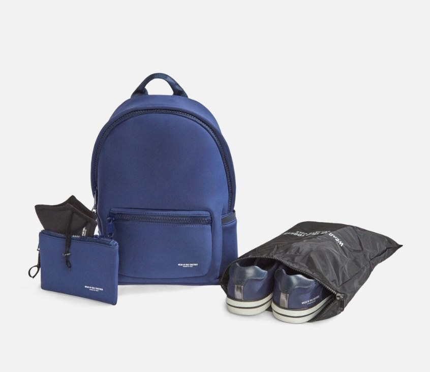 A navy backpack with a matching navy mask pouch and black shoe pouch